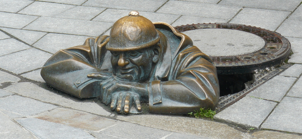 bronze worker emerging from manhole